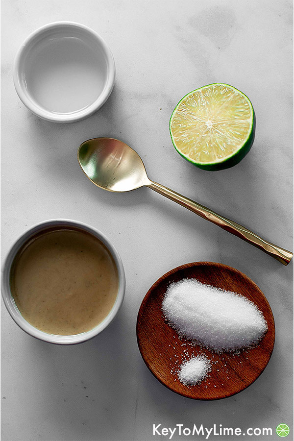 A bowl of tahini, a bowl of water, 1/2 a lime, a plate of sugar and salt, and a spoon on a table.