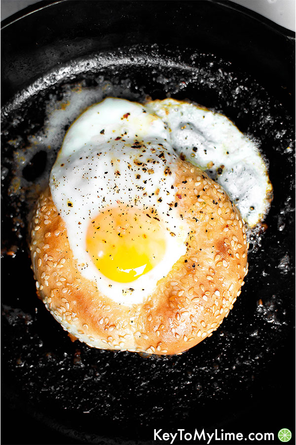 Half bagel in a skillet with a cooked egg in the bagel hole.