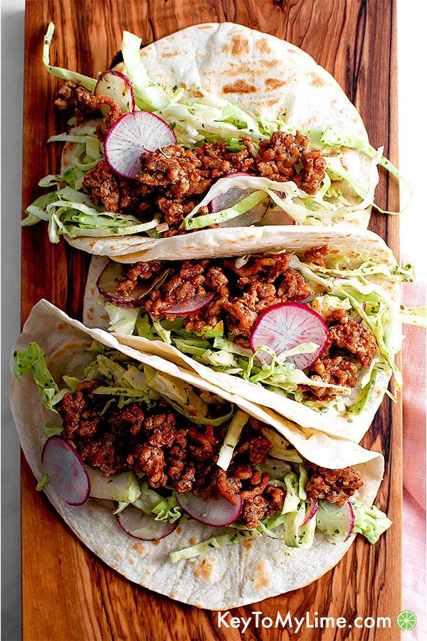 Creamy cilantro turkey tacos on a wooden board.