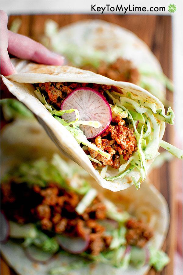 Creamy cilantro turkey tacos in a hand.