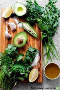 Lime, avocado, garlic, cilantro, parsley, jalapeno, olive oil, and salt on a cutting board.