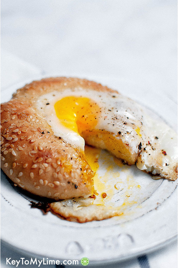 Egg in a hole bagel on a plate with runny yolk and a bite missing.
