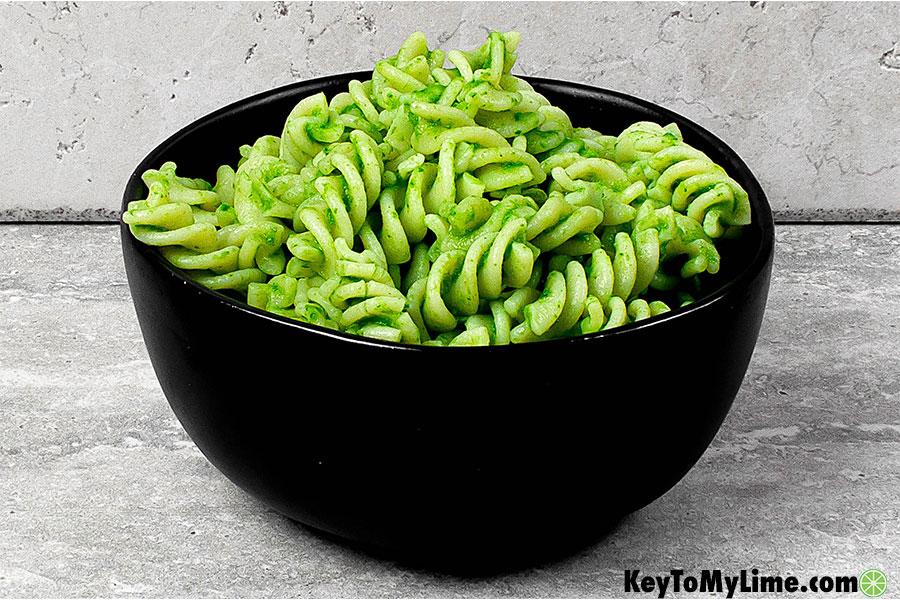 Oil free vegan spinach pesto on pasta in a bowl.