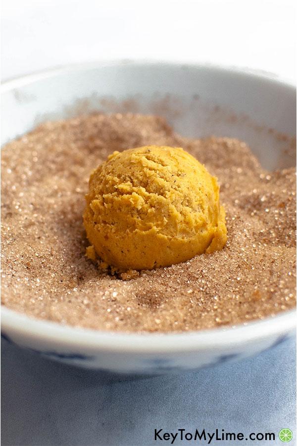 Pumpkin cookie dough in a bowl of sugar.