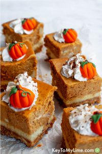 Pumpkin pie cheesecake bars topped with whipped cream.