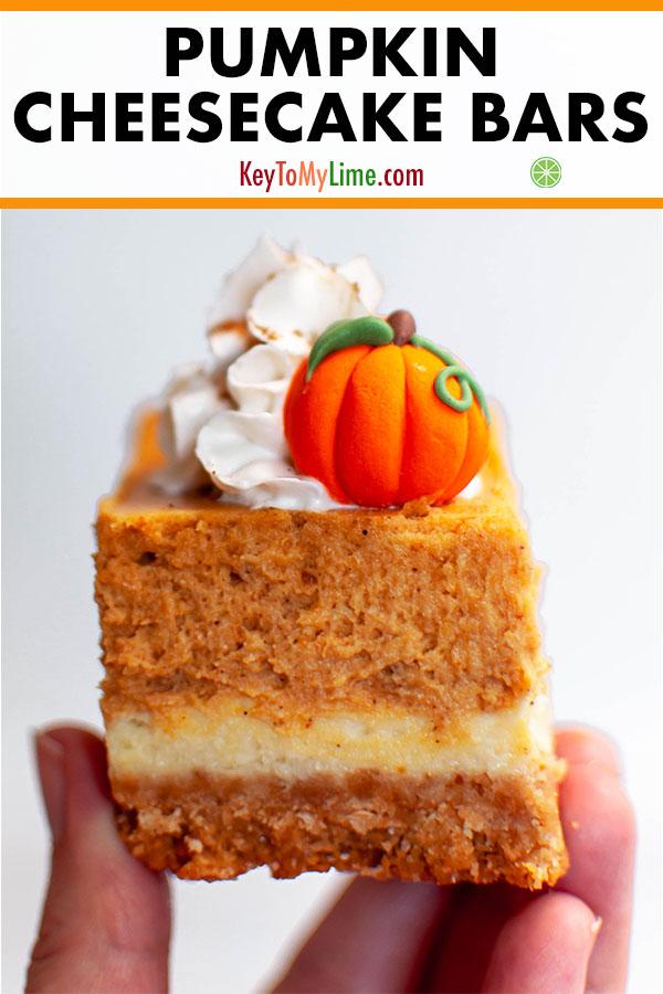 A hand holding a pumpkin pie cheesecake bar.