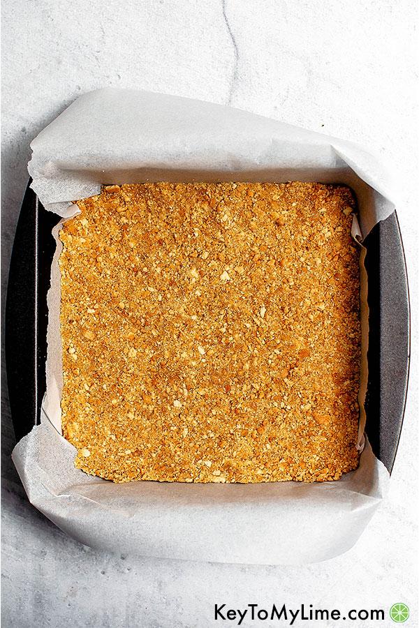Graham cracker crust in a metal baking dish.