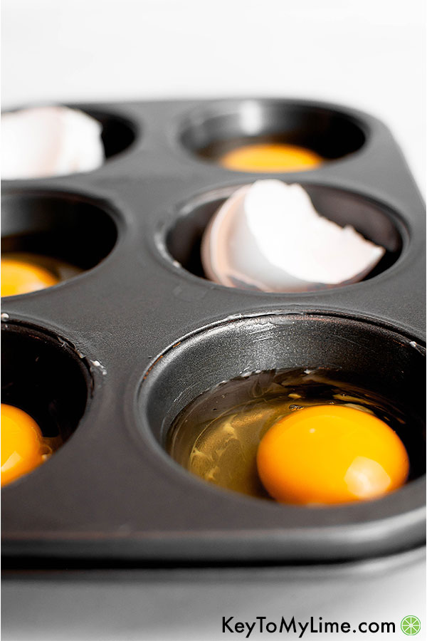 Raw eggs and egg shells in a muffin pan.