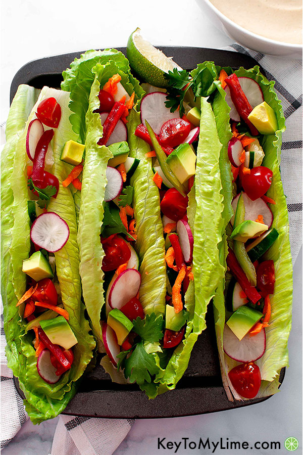 Raw vegan tacos with romaine, avocado, radish, bell pepper, cilantro, cherry tomato, and shredded carrot.