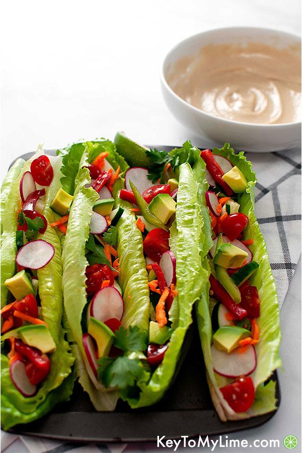 Raw vegan tacos with romaine, avocado, radish, bell pepper, cilantro, cherry tomato, and shredded carrot.