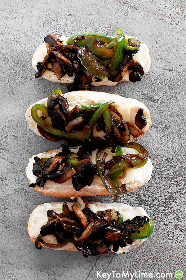 Bread with mayonnaise, cheese, sauteed peppers, onions, and mushrooms on a table.