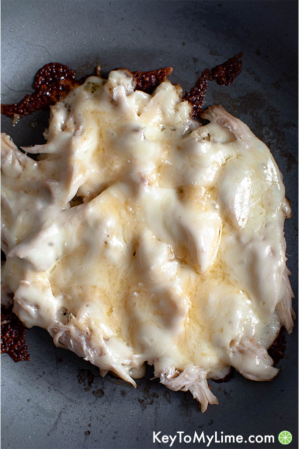 Chicken with melted cheese in a skillet.