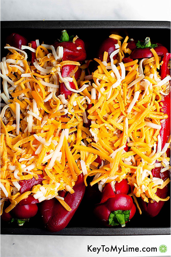 Stuffed peppers covers in shredded cheese.