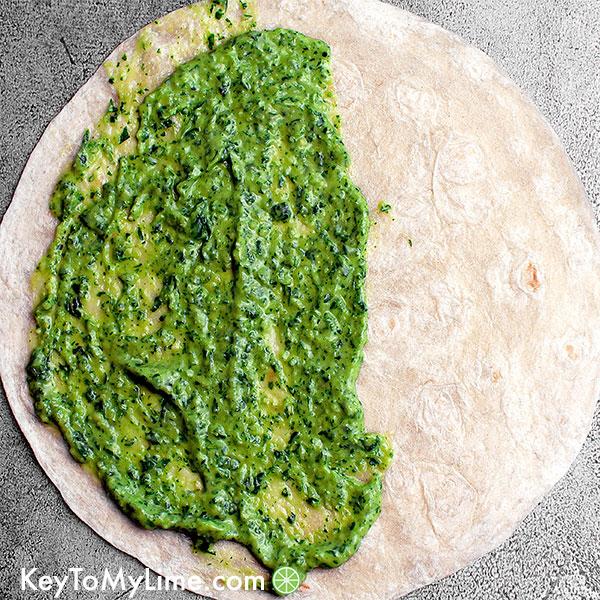 A tortilla with creamy green sauce.