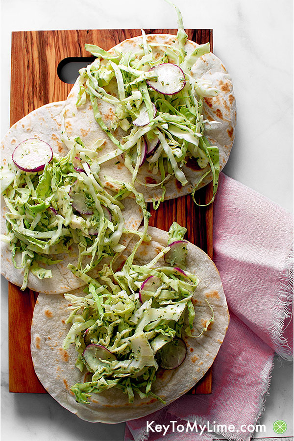 Tortillas with cilantro lime slaw on a wooden board.