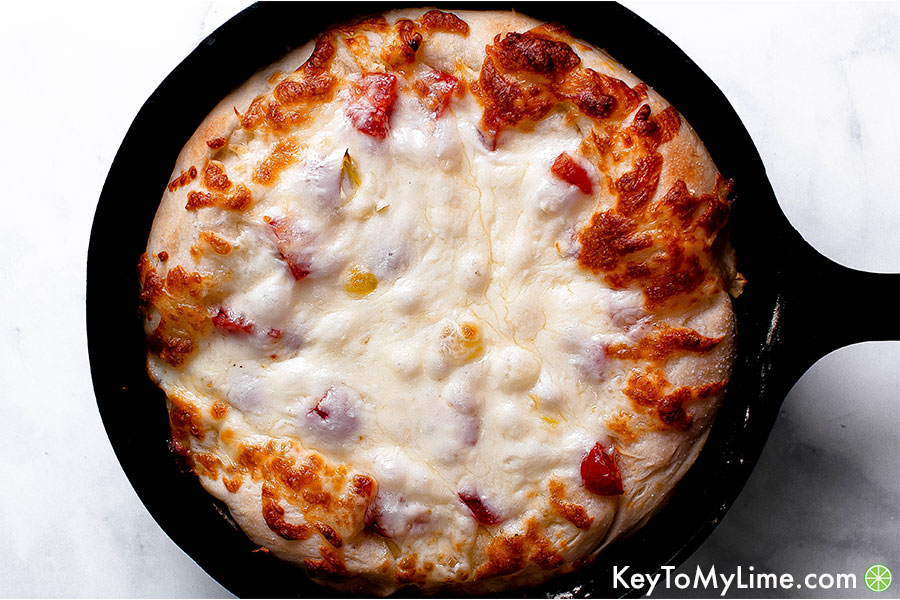 Gluten free pizza crust with cheese in a cast iron skillet.