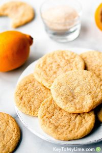 Lemon sugar cookies on a plate surrounded by ingredients.