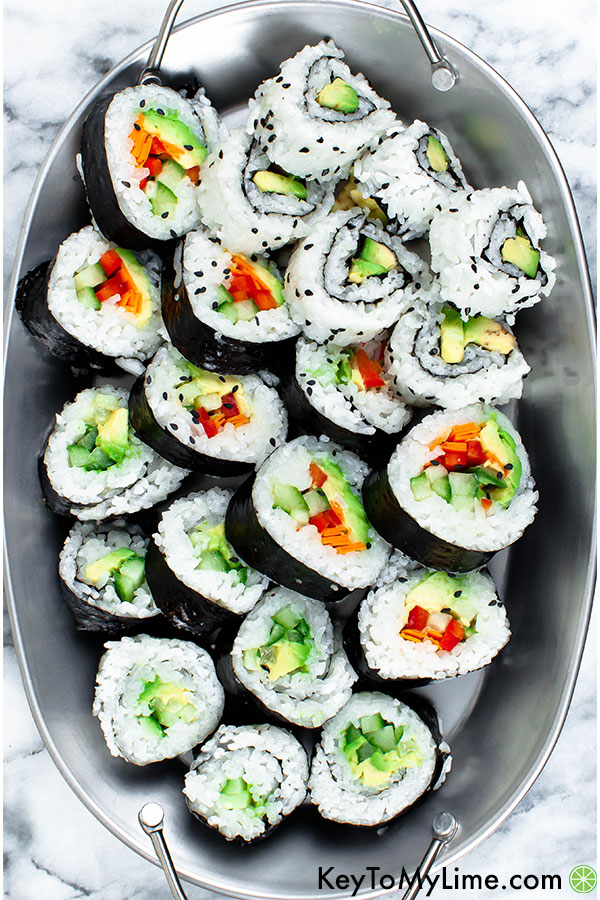 Vegan sushi filled with red bell pepper, carrot, cucumber, and avocado on a platter.