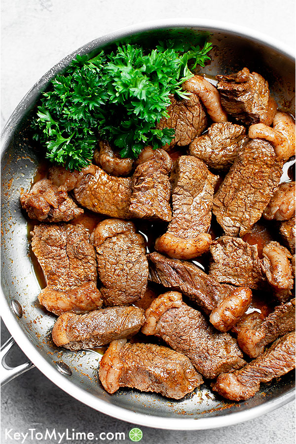 Cooked steak bites in a silver skillet with fresh parsley.