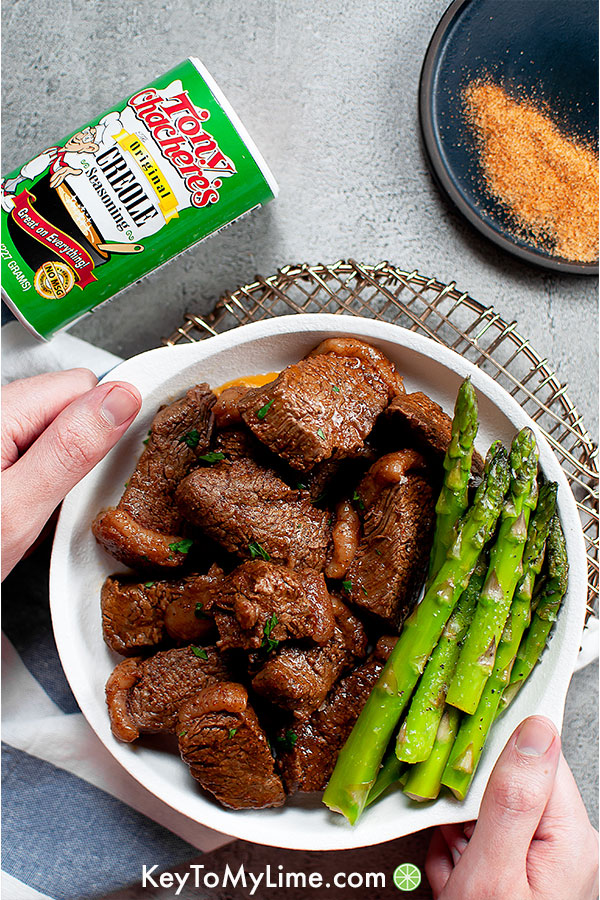 Cajun butter steak bites with asparagus on plate.