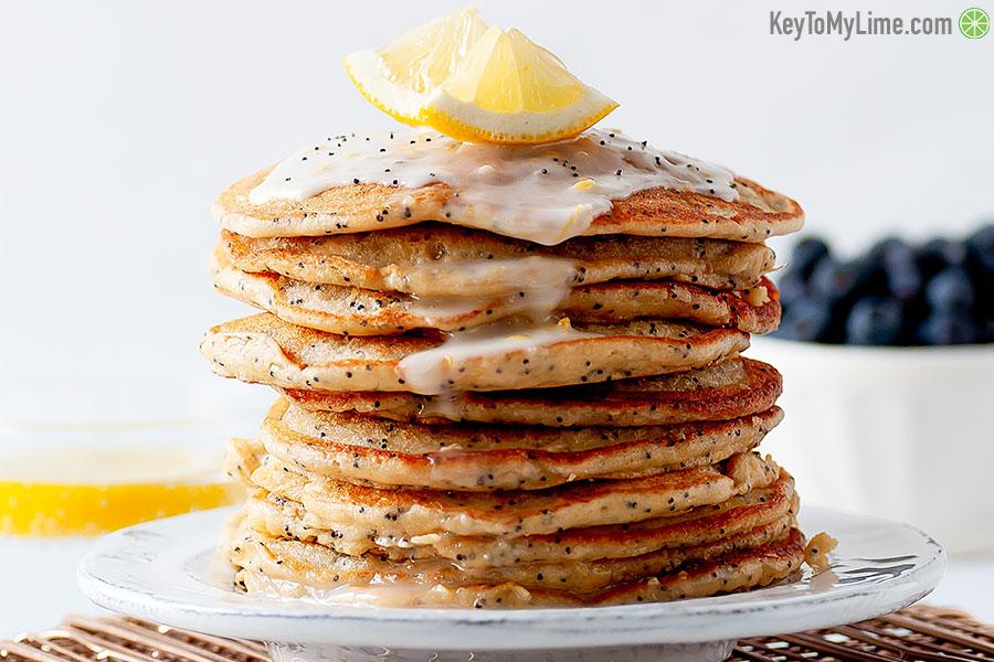 Pancakes with lemon glaze and lemon wedges as garnish.