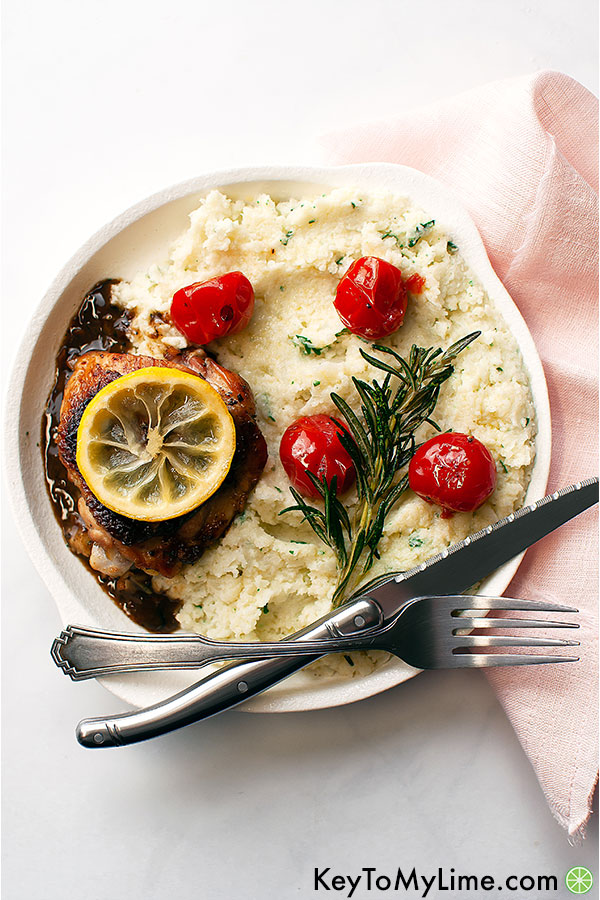Lemon chicken with rosemary on a plate with mashed cauliflower.