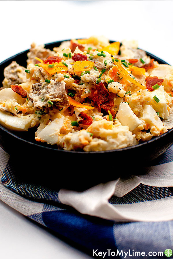Side shot of loaded baked potato salad in a bowl.
