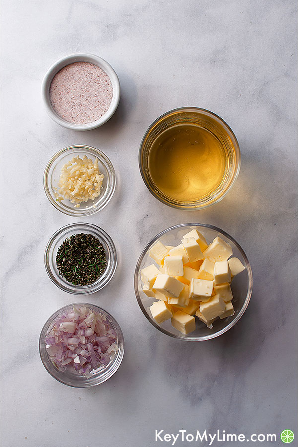 White wine sauce ingredients in small containers on a marble background.