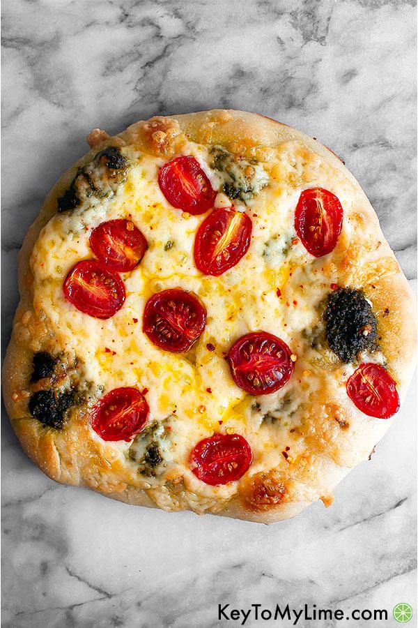 Pesto pizza on a marble board.