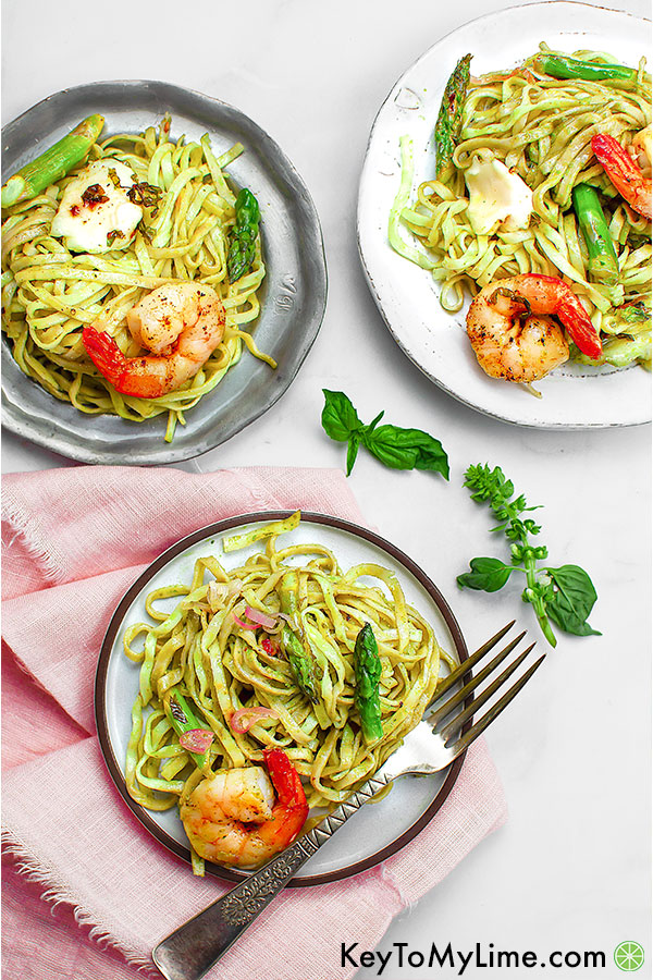 Three plates of shrimp pesto pasta.