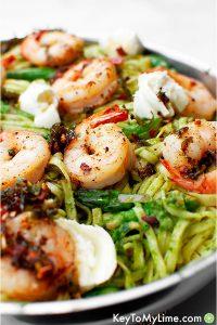 Shrimp pesto pasta in a silver skillet.