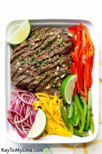 Sliced skirt steak on a white platter with bell peppers and onions.